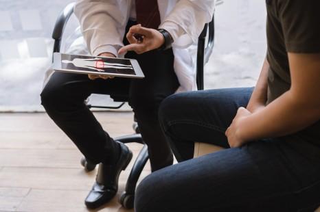 男医生和睾丸癌患者正在讨论睾丸癌检测报告。睾丸癌和前列腺癌的概念。