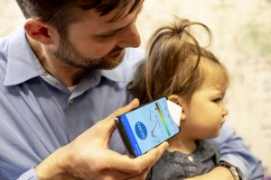 Dr. Randall Bly, an assistant professor of otolaryngology-head and neck surgery at the UW School of Medicine who practices at Seattle Children's Hospital, uses the app to check his daughter's ear.Dennis Wise/University of Washington