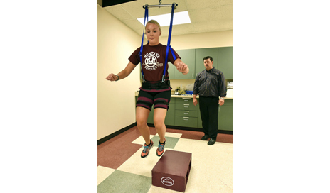 University of Montana graduate student Lauren Astrup does lateral box jumps while demonstrating a physical therapy tool called The Bridge at UM's motion science lab. The device was developed by associate professor Ryan Mizner, right, and a UM student. (Photo courtesy of University of Montana)