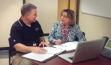 Curt DeWeese, PT, meets with Elaine Spagnola, RN, COHN, to review information about a lost-time employee injury case.