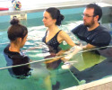 Rachel Mertins, DPT, ATRIC, works on static standing with Elizabeth Dunn, a 25-year-old with a cervical spinal cord injury. Aquatic specialist Erik Schlegel provides a second set of skilled hands to ensure proper alignment and weight-bearing. (Photo Location: PruittHealth – Savannah)