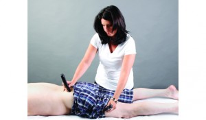Therapist applies DC microcurrent with a handheld device to positively influence the autonomic nervous system and accelerate the body's healing mechanisms for a patient affected by lower back pain.