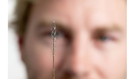 The device, which is the size of a small paperclip, is implanted into a blood vessel next to the brain and is designed to read electrical signals from the motor cortex that are transmitted to an exoskeleton or wheelchair. (Photo courtesy of the University of Melbourne)