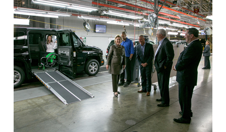 (left to right) Indiana Sen Joe Donnelly, AM General President and CEO Andy Hove, and AM General Commercial President Howard Glaser pause during their tour of the AM General facility with Mrs Clinton to view a demonstration of the MV-1 wheelchair-accessible vehicle from Mobility Ventures. (PRNewsFoto/AM General)